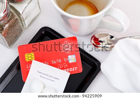 Photo of a credit card placed on a tray to pay for a restaurant bill. The card is a mock up designed and printed by myself, all the details including logos and hologram are generic. - stock photo