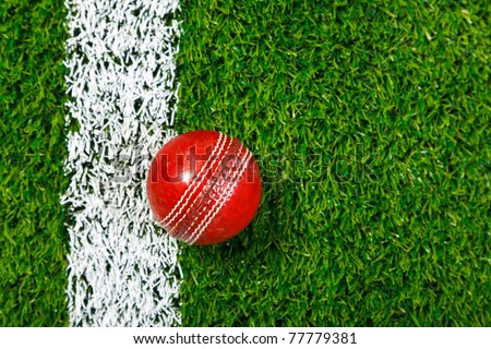 Photo of a cricket ball on a grass next to the white line, shot from above. - stock photo