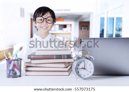 Photo of a cute little girl with science books, alarm clock, and notebook computer on the table. Shot at home