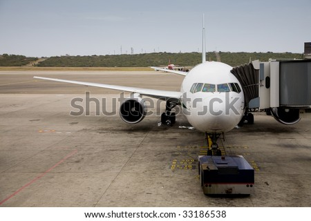 Photo of a docked plane in the airport - stock photo