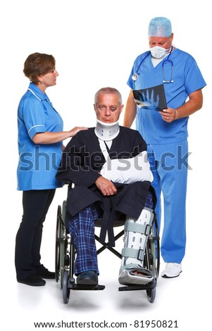 Photo of a doctor in scrubs examining an x-ray of the man in the wheelchairs hand, nurse standing to the side, isolated on a white background. - stock photo