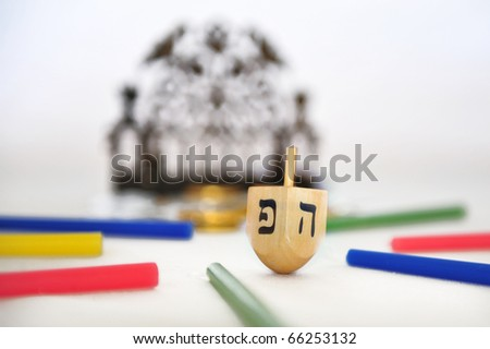Photo of a dreidel (spinning top), a bronze menorah, and colorful candles isolated on white - objects for the Jewish holiday of Hanukkah - stock photo