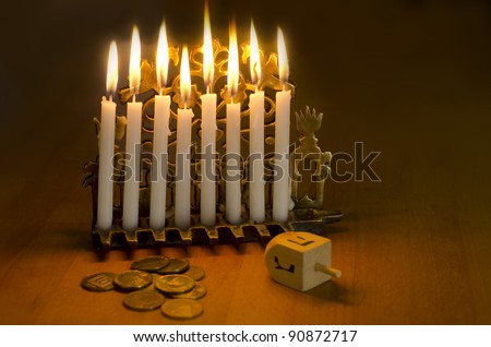 Photo of a dreidel (spinning top), gelts (candy coins) and an ancient brass menorah for the Jewish holiday of Hanukkah. - stock photo