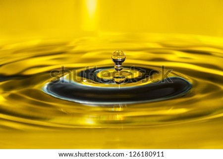 Photo of a drop of water on a yellow background - stock photo