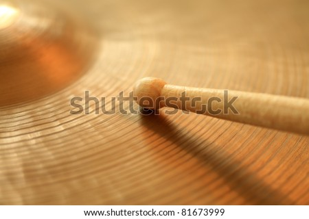 Photo of a drumstick playing on a hi-hat or ride cymbal.  Focus on tip of stick. - stock photo