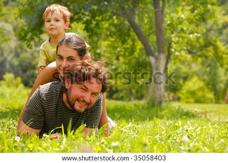 Photo of a family enjoying a summer day on a green meadow - stock photo