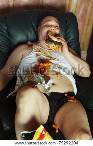 Photo of a fat couch potato eating a huge hamburger and watching television.  Harsh lighting from the television illuminates the dark room. - stock photo