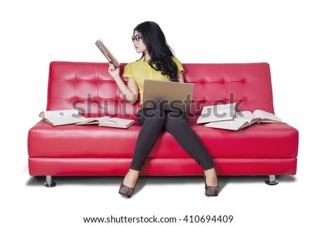 Photo of a female high school student reading books while using notebook computer on the sofa - stock photo