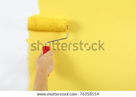 Photo of a female painting a wall with a roller and yellow paint. - stock photo
