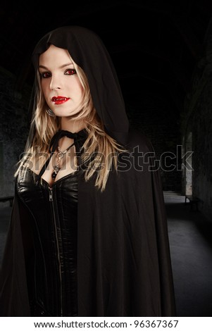 Photo of a female vampire dressed in leather corset and hooded cape.
