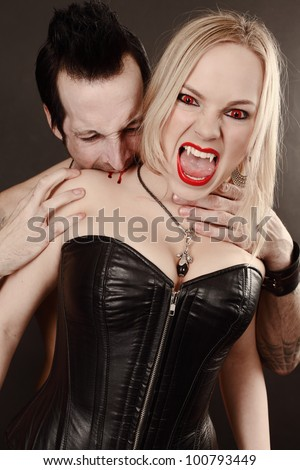 Photo of a female vampire with mouth open and fangs showing being bitten by male vampire.  Desaturated to create pale skin.