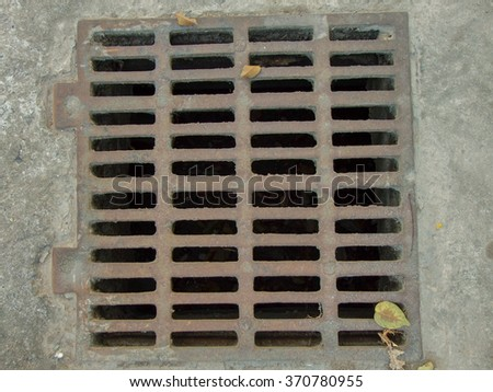 Photo of a fragment of a walking road with rectangular paving tiles and rainwater grating. - stock photo