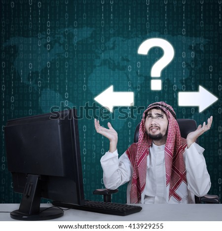 Photo of a frustrated Arabian businessman sitting under question mark and arrow with computer on desk - stock photo