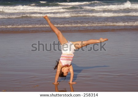 Photo of a girl doing cartwheels at the beach.