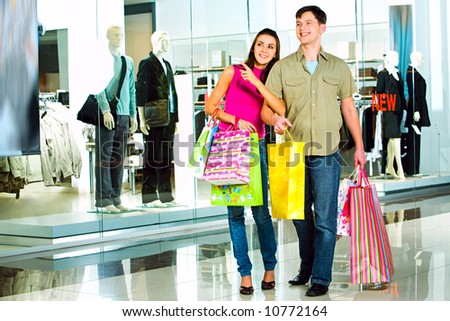 Photo of a girl looking attentively and pointing at something in the shopping centre with handsome man near by - stock photo
