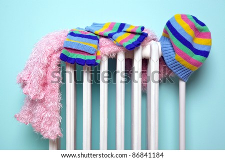 Photo of a girls hat, scarf and gloves drying on an old traditional cast iron radiator, good image for winter related themes. - stock photo