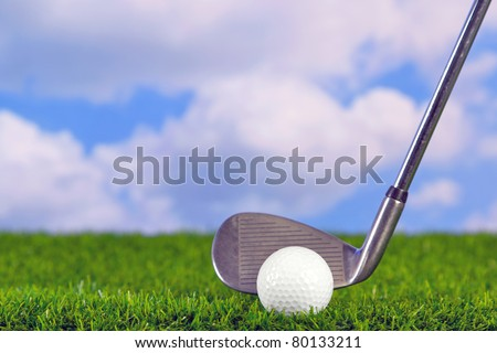 Photo of a golf iron club behind the ball on the fairway. - stock photo