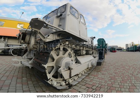 Photo of a gray bulldozer among the railway trains. Strong distortion from the fisheye lens