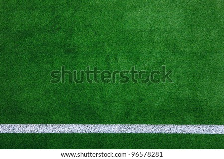 Photo of a green synthetic grass sports field with white line shot from above. - stock photo