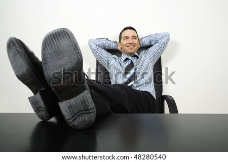 Photo of a happy businessman reclining with his feet up and hands behind his head. - stock photo