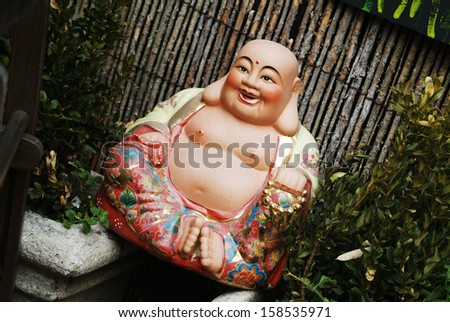 photo of a happy smiling Buddha figuring in a garden - stock photo