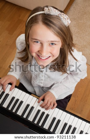 Photo of a happy young girl playing the piano at home. - stock photo