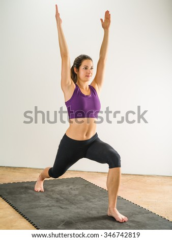 Photo of a healthy young woman doing the warrior yoga position on a black floor mat. - stock photo