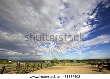 photo of a horse corral with a horse and beautiful  blue sky's above with big white puffy clouds - stock photo