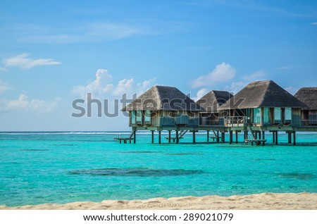 Photo of a hotel cabanas over the water of Maldives clear beach  - stock photo
