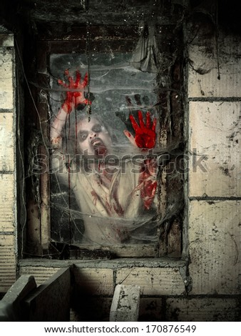Photo of a hungry zombie covered with blood at the window. - stock photo