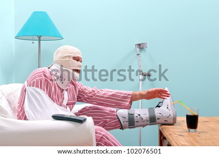 Photo of a injured man in pyjamas with a bandaged head, leg cast, arm sling and neck brace struggling to reach a drink on the table in front of him. - stock photo