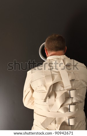 Photo of a insane man in his forties wearing a straitjacket looking out the hole of an asylum door. - stock photo