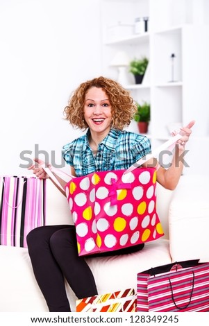 Photo of a joyful lady opening a shopping bag at home