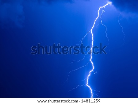 Photo of a lightning during a thunderstorm on a background of the dark dark blue sky