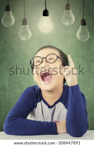Photo of a little boy get an idea in the classroom and pointing at bright light bulb - stock photo