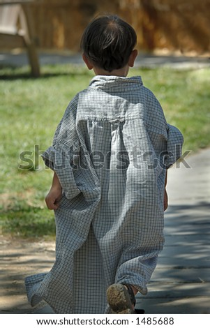 """Photo of a little boy wearing his daddy's very big shirt (after having an unfortunate """"accident"""" ;-) - stock photo"""