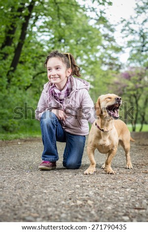 Photo of a little girl kneeling in the park with a dog - stock photo