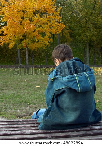 Photo of a lonely boy is sitting on a bench in an autumn park. Back view.