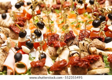 photo of a lot of snacks with skewers and sandwiches on buffet table