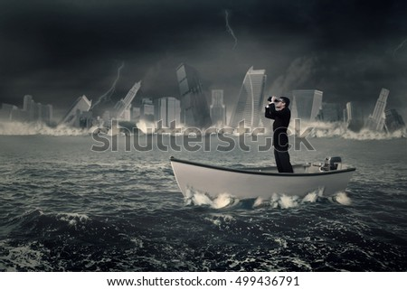Photo of a male businessman standing on the boat while looking through binoculars with a sinking town at the sea