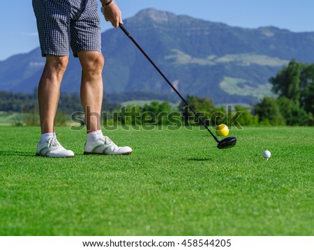 Photo of a male golfer teeing off on a golf course on a beautiful day. - stock photo