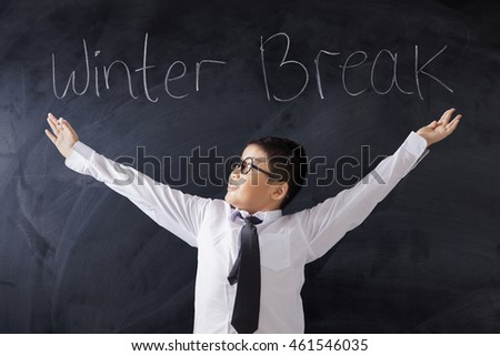 Photo of a male primary school student standing in the classroom with text of Winter Break on the blackboard