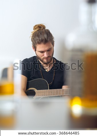 Photo of a male songwriter with acoustic guitar taken between a blurred whisky bottle and rocks glass. - stock photo