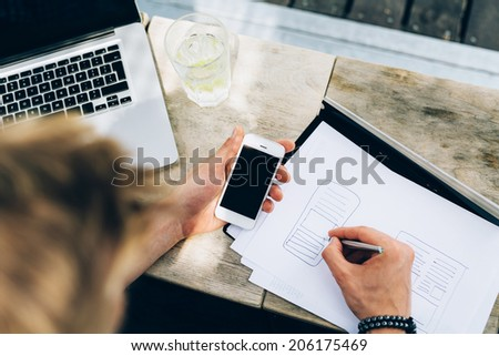 Photo of a man drawing a blueprint of a mobile application - stock photo