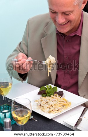 Photo of a man eating pasta in an Italian restaurant. - stock photo