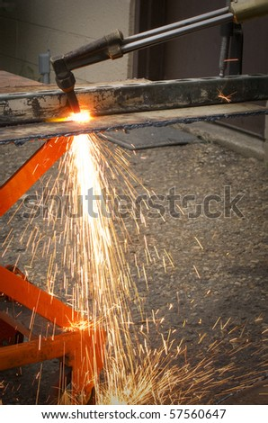 photo of a man flame cutting steel plate - stock photo