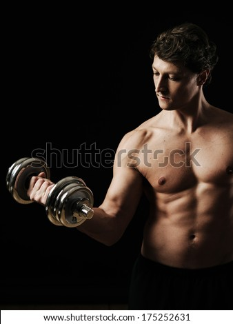 Photo of a man in his early thirties doing bicep curls with a dumbbell over a black background. - stock photo