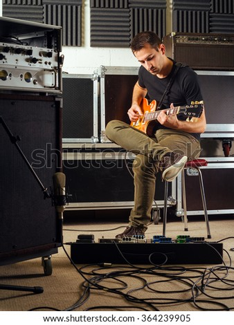 Photo of a man in his late 20's sitting in a recording studio practicing his guitar playing. - stock photo