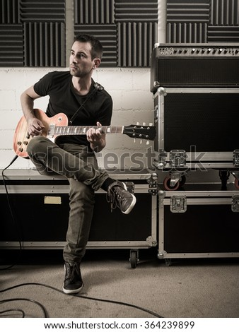 Photo of a man in his late 20's sitting in a rehearsal studio practicing his guitar playing. - stock photo