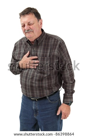 Photo of a man in his sixties suffering pain from a heart attack or severe indigestion. - stock photo